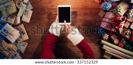 Santa Claus sitting at his desk and using a digital touch screen tablet surrounded by colorful Christmas gifts - stock photo