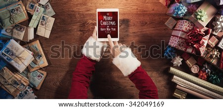 Santa Claus sitting at his desk and using a digital touch screen tablet surrounded by colorful Christmas gifts, Merry Christmas and Happy New Year message - stock photo