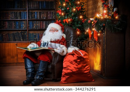 Santa Claus sitting at his home in a comfortable chair and reading a letter.  - stock photo