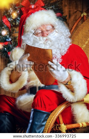 Santa Claus sitting at his wooden house in a comfortable chair and reading a letter.