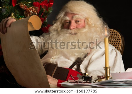 Santa Claus sitting at home and reading old paper roll to do list at night with candle light. Authentic vintage style portrait.