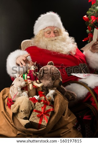 Santa Claus sitting at home at comfortable armchair holding envelope and reading children's letters and wishes and choosing toys from big sack near him.