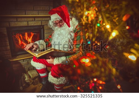Santa Claus sitting at home near Christmas tree and  resting by his fireplace - stock photo