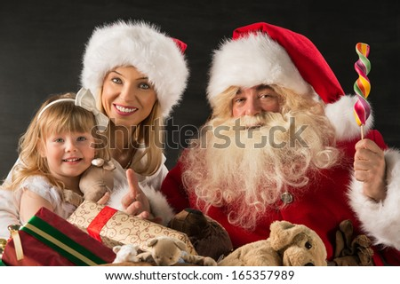 Santa Claus sitting at home with family - little girl and her mother and giving gifts - stock photo