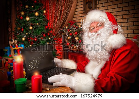 Santa Claus sitting at the table with a laptop at his home. Christmas time. - stock photo