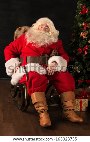 Santa Claus sitting in a comfortable rocking chair near the Christmas tree at home - stock photo