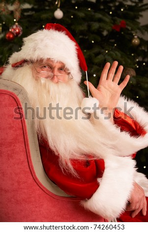 Santa Claus Sitting In Armchair In Front Of Christmas Tree - stock photo