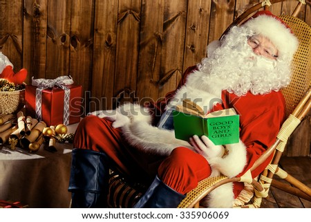 Santa Claus sitting in his wooden house in a comfortable chair and prepare gifts for Christmas. He checks his list in a notebook. - stock photo