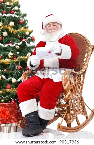 Santa Claus sitting in rocking chair and reading letter with children wish - stock photo
