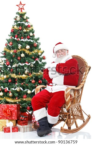 Santa Claus sitting in rocking chair next full decorated Christmas tree, isolated on white background - stock photo