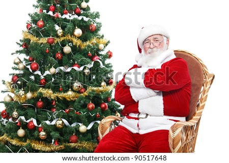 Santa Claus sitting in rocking chair with crossed arms and relax, decorated Christmas tree, isolated on white background - stock photo