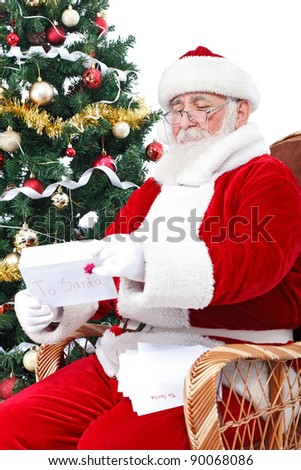 Santa Claus sitting next Christmas tree and reading children  letters for Christmas - stock photo