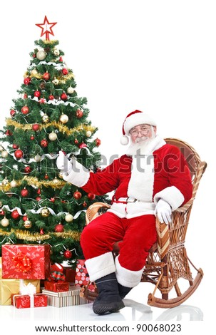 Santa Claus sitting next Christmas tree showing thumb-up sign, isolated on white background - stock photo