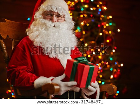 Santa Claus sitting on background of sparkling firtree - stock photo