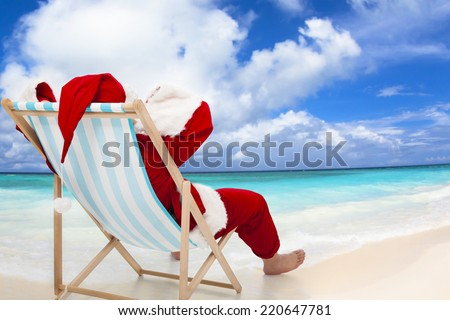 Santa Claus sitting on beach chairs with blue sky and cloud.Christmas Day concept. - stock photo