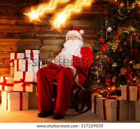 Santa Claus sitting on rocking chair in wooden home interior with gift boxes around him and two falling stars