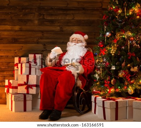 Santa Claus sitting on rocking chair in wooden home interior with letters in hands - stock photo