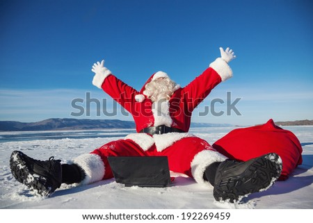Santa Claus sitting on snow glad news in the laptop, shooting was conducted in a sunny day on lake Baikal - stock photo