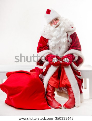 Santa Claus sitting on the bench on white background. Isolated - stock photo