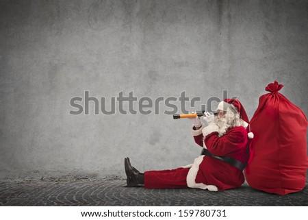 Santa Claus sitting on the floor looking through spyglass - stock photo