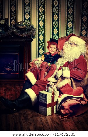 Santa Claus sitting with a little cute boy elf near the fireplace at home. - stock photo