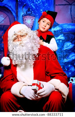Santa Claus sitting with a little cute boy elf over Christmas background. - stock photo