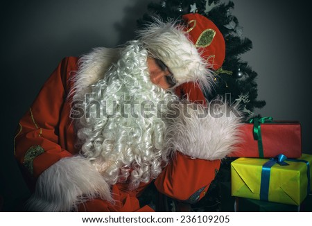 Santa Claus sleeping next to Christmas tree and gifts.