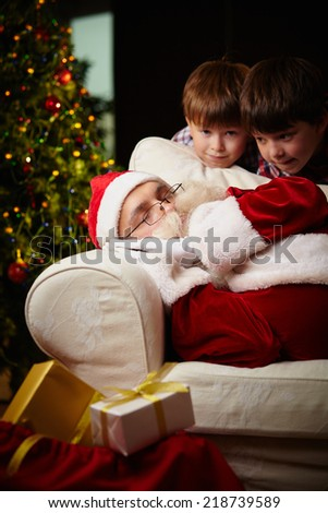 Santa Claus sleeping with two boys near by and giftboxes - stock photo