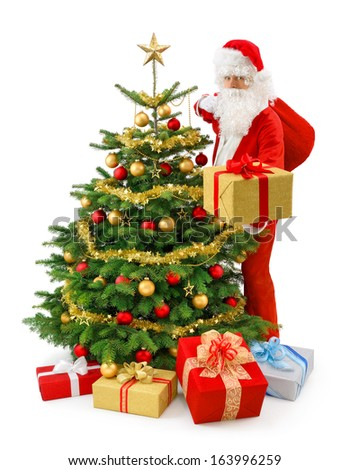 Santa Claus standing beside a gorgeous Christmas tree and presenting a gold gift box - stock photo