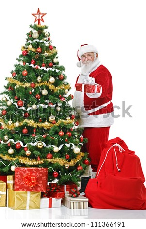 Santa Claus standing next decorated  Christmas tree and holding gift and, isolated on white background - stock photo