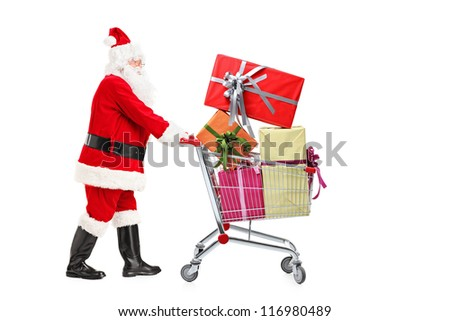 Santa Claus standing next to a shopping cart full of gifts isolated on white background - stock photo
