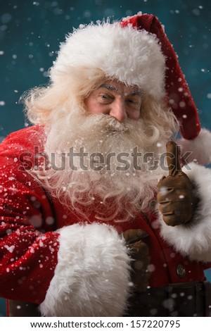 Santa Claus standing outdoors at snowfall at north pole and showing thumb up - stock photo