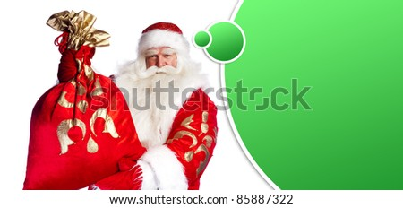 Santa Claus standing up on white background with his bag full of gifts. Blank balloon with lots of copyspace for your text and logo overhead - stock photo