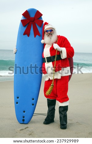Santa Claus stands on the beach by the Ocean holding a Blue Surfboard with a Large Red Bow on it as a Christmas Gift to some lucky Boy or Girl. Santa Claus is one cool cat and love to give things out - stock photo