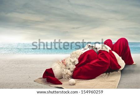 Santa Claus sunbathing lying on the beach - stock photo