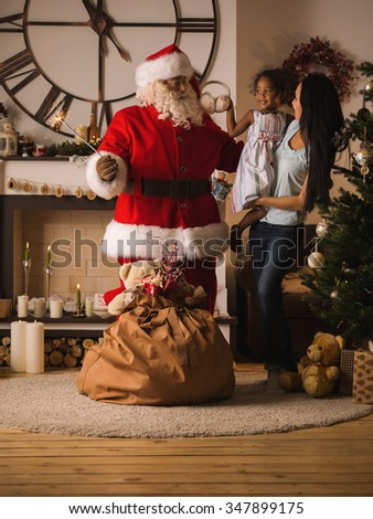 Santa Claus Surprising little Girl and her Mother at Home - stock photo