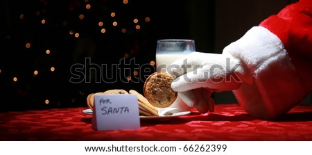 Santa Claus takes a cookie left out for him on Christmas Eve as a thank you gift for leaving presents to a grateful boy or girl - stock photo