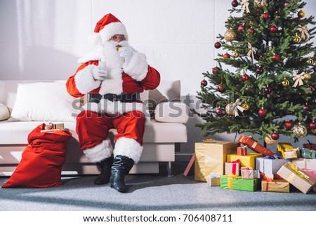 santa claus taking medicines while sitting on sofa at home