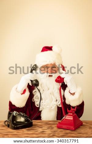 Santa Claus talking by phones. Christmas holiday concept - stock photo