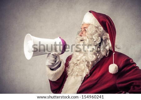 Santa Claus talking with megaphone - stock photo