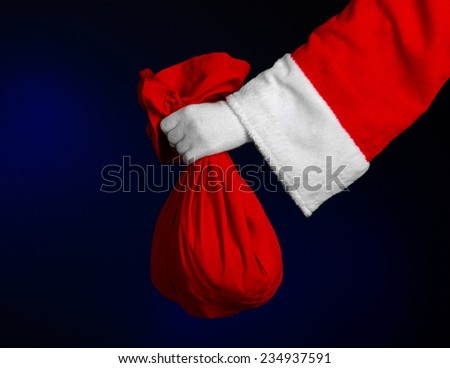 Santa Claus theme: Santa holding a big red sack with gifts on a dark blue background