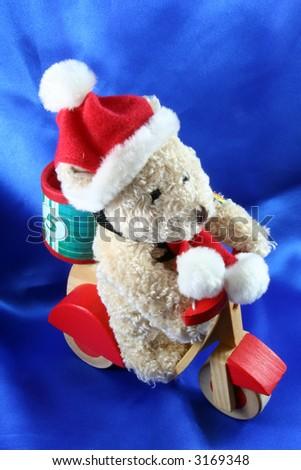 santa claus toy teddy bear on blue satin background - stock photo