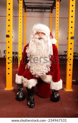 Santa Claus training before Christmas in gym - kettlebells - stock photo