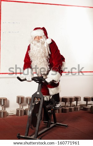 Santa Claus training on exercise bike at the gym - stock photo
