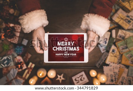 Santa Claus using a digital touch screen tablet with Merry Christmas and Happy New Year message, hands close up - stock photo