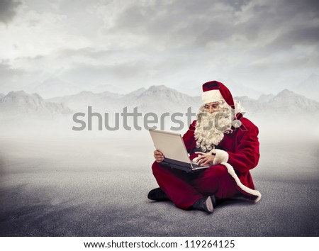 Santa Claus using a laptop computer in a wasteland - stock photo