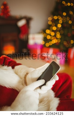 Santa claus using a smartphone at christmas at home in the living room