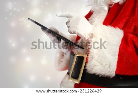 Santa Claus using a tablet in snowy night - stock photo