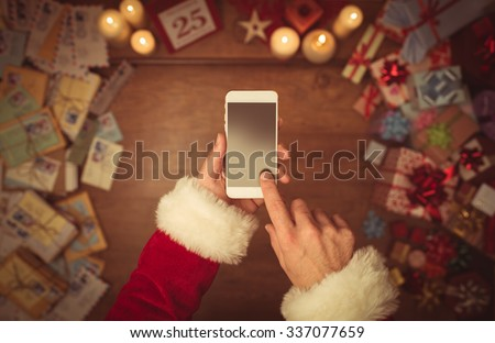 Santa Claus using a touch screen smart phone, hands close up, top view, desktop with gifts and Christmas letters on background