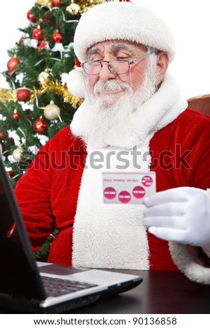 Santa Claus using computer purchasing on internet paying with credit card - stock photo
